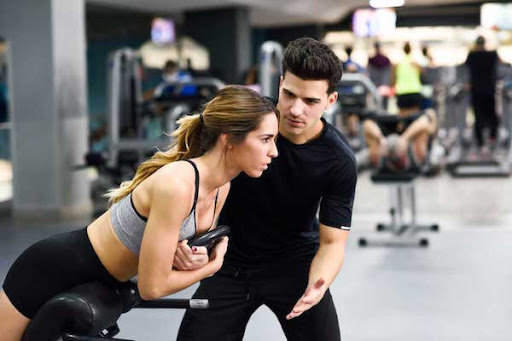 Femme en salle de sport avec un coach sportif