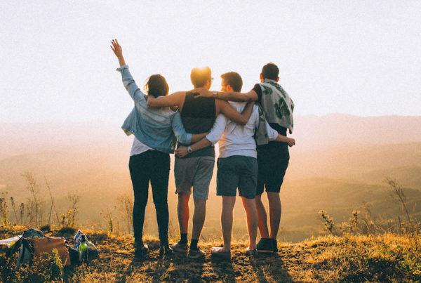 4 amis sur une colline face au soleil